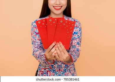 Beautiful asian woman on traditional festival costume Ao Dai holding lucky pocket money