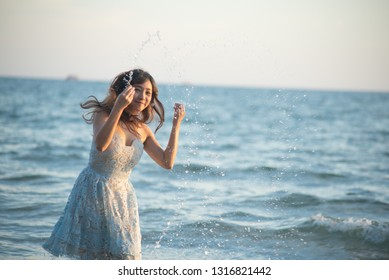 Beautiful asian woman on tropical beach. Portrait of happy young woman smiling at sea in summe.