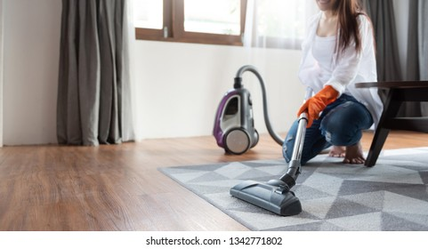 Beautiful Asian woman in orange protective gloves using vacuum cleaner on the rug or carpet.