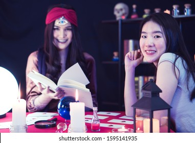 A beautiful Asian woman is performing a ritual for fortune telling with the fortune teller, a woman with a third eye and a sixth sense in a mysterious dark room.