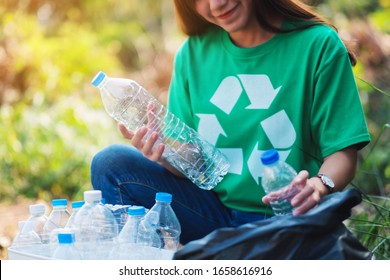 A beautiful asian woman picking up garbage plastic bottles into a box and bag for recycling concept