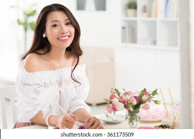Beautiful Asian woman planning menu for buffet dinner