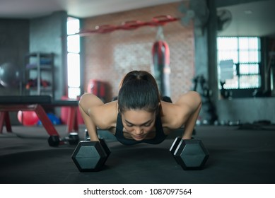 Beautiful asian woman play fitness in the gym,Thailand girl has a slim body,Time for exercise,People love heath,Stretching body before workout,Sport woman warm up body,push up with dumbell