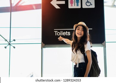Beautiful asian woman point the sign toilets at airport terminal with luggage suitcase and backpack for travel in vacation summer relaxing waiting flight transport