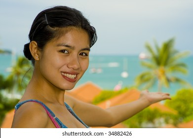 beautiful asian woman pointing to the sea