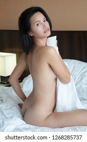 Beautiful Asian woman posing nude on a bed with white sheets