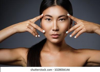 Beautiful asian woman is posing in studio