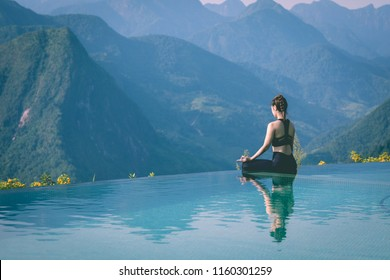 Beautiful Asian woman practice yoga Lotus pose on the pool above the Mountain peak in the morning in front of beautiful nature views in SAPA vietnam,Feel so comfortable and relax with yoga in holiday