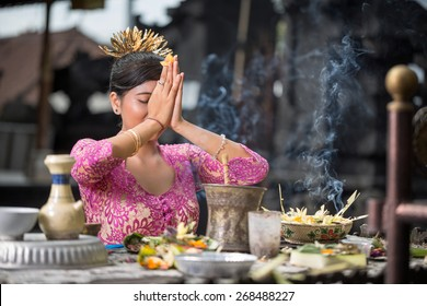 Beautiful Asian woman prays in the temple. Bali. Indonesia
