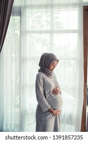 beautiful asian woman pregnant wearing hijab standing next to window