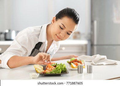 Beautiful Asian woman preparing dish with shrimps at table in kitchen