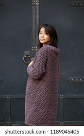 beautiful Asian woman with puple knitted cardigan stands with her back turned her head into a camera.