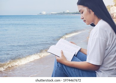 beautiful Asian woman reads a book or the holy bible while sitting at the seaside. Relax reading book with seascape background. Christian devotional or bible study concept with copy space.