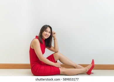 Beautiful asian woman in red dress sit on floor pose for take a photo on white background,slim girl with smile