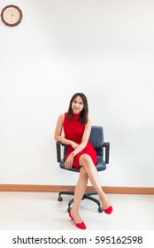 Beautiful asian woman in red dress pose for take a photo on the chair on white wall background,slim girl with smile,office sexy lady concept