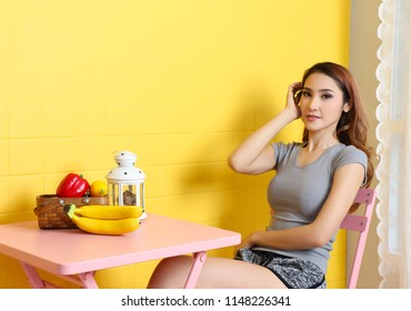 beautiful asian woman relax in studio and yellow background