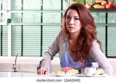 Beautiful asian woman relaxing in kitchen