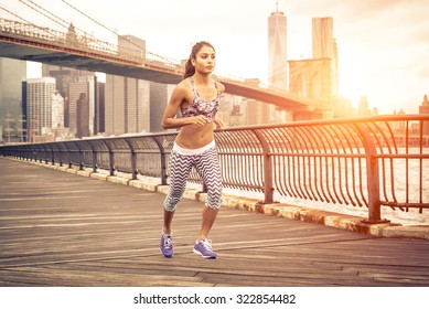 beautiful asian woman running in New york at sunset time. Brooklyn bridge and Manhattan skyline in the background