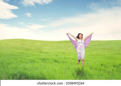 Beautiful asian woman running on field. Summer or Spring concept