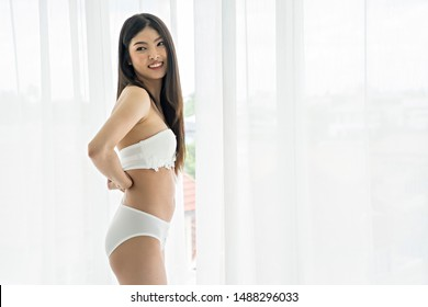 A beautiful Asian woman sexy in a bedroom in the house.