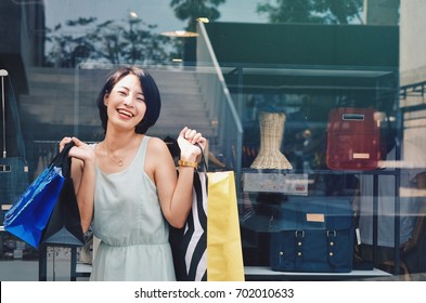 Beautiful Asian woman with shopping bag in front of outlet mall.
