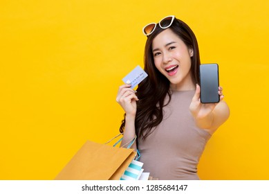 Beautiful Asian woman with shopping bags showing credit card and smartphone in hands for mobile financial appication concept