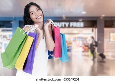 Beautiful Asian woman with shopping bags in duty free in International Airport before departure. Sale, shopping, tourism and happy people concept.