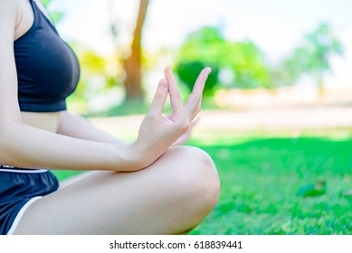 Beautiful asian woman sit on the lawn for play yoga in the park at daylight,slim girl love healthy of self,Yoga is an exercise that makes you feel very good
