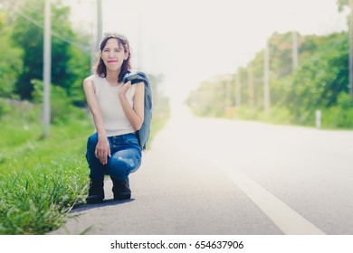 beautiful asian woman sit on the roadside wait for the car,hitchhiker travel concept