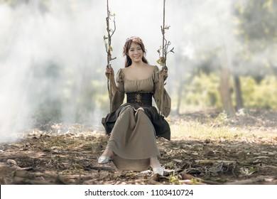 Beautiful Asian woman sits swing in the garden.