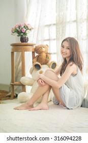 Beautiful asian woman sitting among morning sunshine