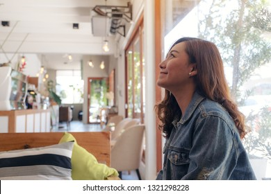 A beautiful asian woman sitting in cafe with feeling happy