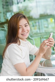 Beautiful asian woman sitting in cafe and using a smartphone .