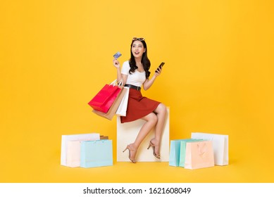 Beautiful Asian woman sitting and carrying shopping bags with credit card and mobile phone in hands on yellow background