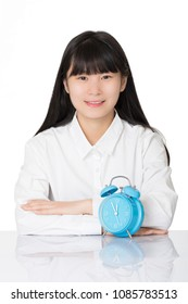 Beautiful Asian woman sitting at a desk smiling with a blue alarm clock isolated on a white background
