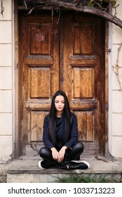 Beautiful Asian woman sitting in front of old door