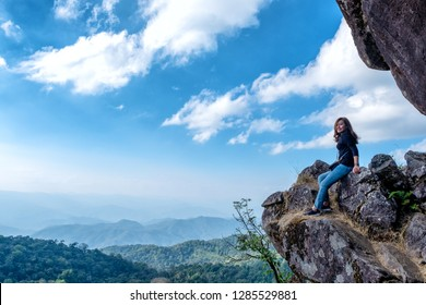 A beautiful asian woman sitting on a cliff with mountains view and blue sky background