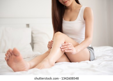 Beautiful Asian woman sitting on a bed and applying body lotion on her legs.