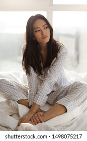 Beautiful Asian woman sitting on the bed in her room at home. Calm young girl in nightgown with long hair relaxing in bed indoors in sunny morning. Time to wake up. daily routine, regime.