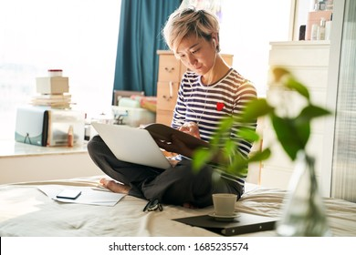 Beautiful Asian woman sitting on bed & working from home on laptop