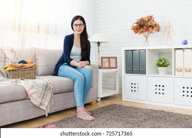 beautiful asian woman sitting on sofa ready to make knitting for winter coming in the living room at home