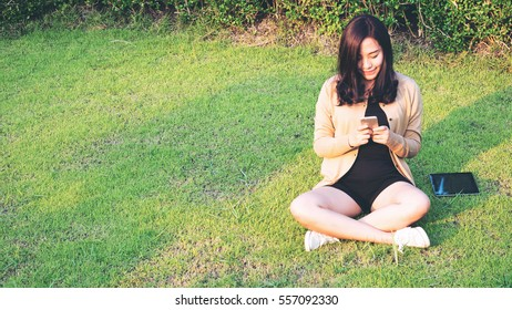 An beautiful asian woman sitting and using smart phone on green grass at the park with smiling face