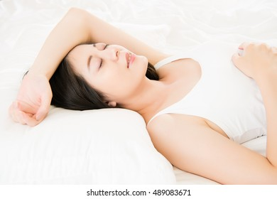 beautiful Asian woman sleep smile on bed comfortably in the morning, indoor bedroom background