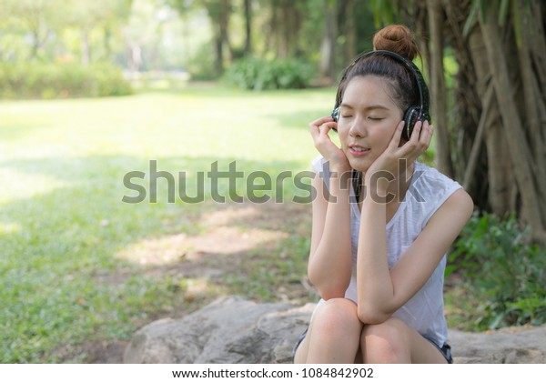 beautiful asian woman smile and relaxing by listen to music from stereo headphones in garden. with copy space for text