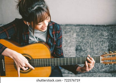 A beautiful asian woman smile while playing acoustic guitar and listening to music,sitting on sofa at home
