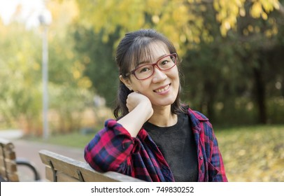 Beautiful asian woman smiling enjoy the sunshine in the park in autumn