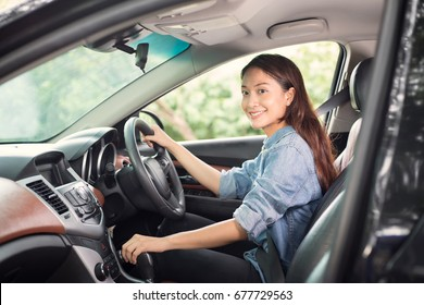 Beautiful Asian woman smiling and enjoying driving a car and hand is about to drive into gear on road for travel