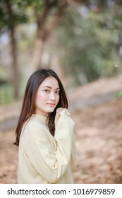 Beautiful Asian woman Smiling happy girl and wearing warm clothes winter and autumn portrait at outdoor in park