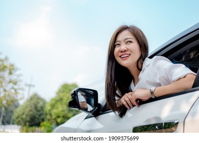 Beautiful Asian woman smiling and looking at the sky in a white car.