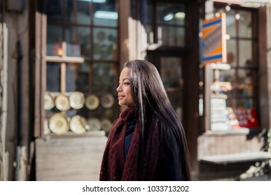 Beautiful Asian woman smiling while strolling the street